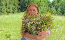 Het meisje koestert de bloemen Het meisje houdt een boeket van bloemen Meisje met Gesloten Ogen Boeket met de zomerbloemen Royalty-vrije Stock Foto's