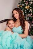 Het meisje koestert haar moederzitting dichtbij een Kerstboom in de weelderige blauwe avondjurken royalty-vrije stock foto's