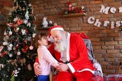 Het meisje koestert Santa Claus en maakt wens voor Kerstmis in coz stock afbeeldingen