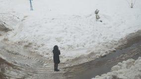 Het meisje komt aan een vulklei en gaat door de natte sneeuw terug stock videobeelden