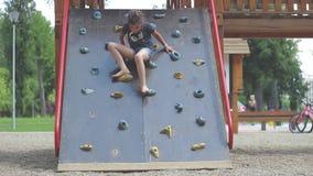 Het meisje komt neer bij het beklimmen van muur in de openbare speelplaats stock videobeelden