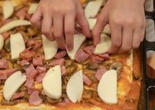 Het meisje kookt pizza De handen van het kind maken plakken van mozarellakaas op op een pizza stock foto's