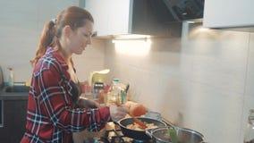 Het meisje kookt voedseltribunes bij het fornuis die in een rooster braden bevindt zich binnen in de keuken vrouw die door het fo stock footage