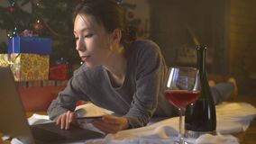 Het meisje koopt heden online door creditcard dichtbij Kerstmisboom stock videobeelden