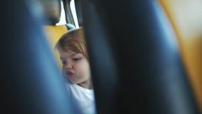 Het meisje kronkelt zich in de achterbank van een auto stock footage