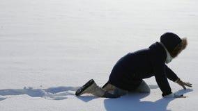 Het meisje kruipt op alle fours in diepe sneeuw stock videobeelden