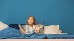 Het meisje kruipt op het bed en bepaalt stock footage