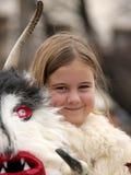 Het meisje Kuker, jonge geitjesmummers voert rituelen met kostuums en grote klokken op internationaal festival van maskeradespele Stock Afbeelding