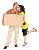 Het meisje kust de kerel houdend een doos Stock Afbeelding