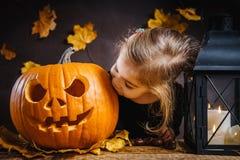 Het meisje kust een Halloween-pompoen Royalty-vrije Stock Afbeeldingen