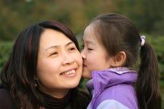 Het meisje kust haar moeder Stock Afbeeldingen