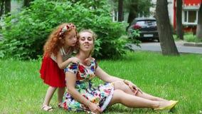 Het meisje kust haar moeder op gazon in de zomerpark stock footage