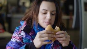 Het meisje kwam de koffie van de straat tegen, die snel zou eten Het brunette zit in een blazer en eet a stock footage