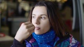 Het meisje kwam de koffie van de straat tegen, die snel zou eten Het brunette zit in een blazer en eet het Frans stock video