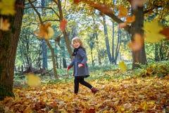 Het meisje lacht en speelt met de herfstbladeren stock foto's