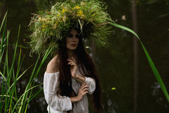 Het meisje in lange kleding en kroon dompelt in rivier onder Royalty-vrije Stock Afbeelding