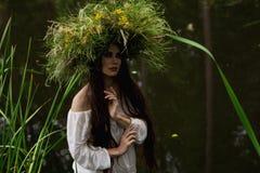 Het meisje in lange kleding en kroon dompelt in rivier onder Stock Foto's