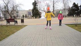 Het meisje leert aan rolschaats op bedekte weg in Park Familievakantie in het Park stock video