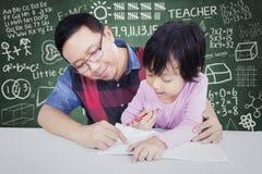 Het meisje leert in de klasse met mannelijke leraar Royalty-vrije Stock Foto