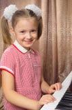 Het meisje leert om een piano te spelen stock foto