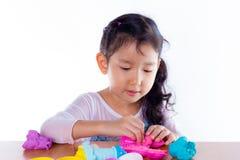 Het meisje leert om kleurrijke plasticine te gebruiken Stock Foto