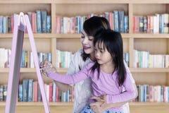 Het meisje leert om met krijt te schrijven Stock Fotografie