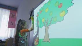 Het meisje leert vruchten met computerprogramma en projector stock video