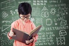 Het meisje leest boek met krabbels op bord Stock Foto's