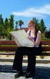 Het meisje leest de kaart. Stock Foto