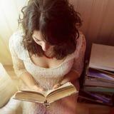 Het meisje leest een boek door het licht van lamp Mening vanaf top down royalty-vrije stock afbeelding