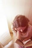 Het meisje leest een boek door het licht van lamp Mening vanaf top down stock fotografie