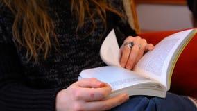 Het meisje leest een boek in een woonkamer stock footage