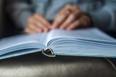 Het meisje leest een open boek, dat op haar overlapping ligt royalty-vrije stock foto