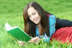 Het meisje leest het boek Stock Afbeeldingen