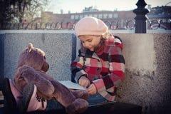 Het meisje leest het boek aan een stuk speelgoed draagt Stock Foto