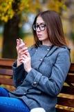 Het meisje leest sms, herschreven smartphone in openlucht in de lente of de herfst, op de bank, met koffiethee, ontbijt, concep Stock Foto's