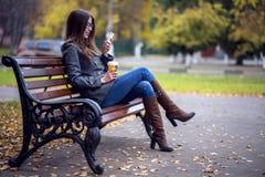 Het meisje leest sms, herschreven smartphone in openlucht in de lente of de herfst, op de bank, met koffiethee, ontbijt, concep Stock Afbeelding