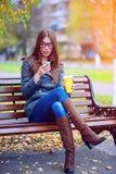 Het meisje leest sms, herschreven smartphone in openlucht in de lente of de herfst, op de bank, met koffiethee, ontbijt, concep Stock Fotografie
