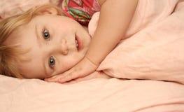 Het meisje legt in een bed Royalty-vrije Stock Afbeelding