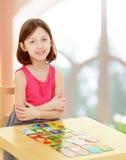 Het meisje legt kaarten op de lijst stock fotografie