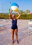 Het meisje leidt met de bal op om volleyball in de pool bij zon te spelen Stock Foto