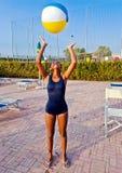 Het meisje leidt met de bal op om volleyball in de pool bij zon te spelen Royalty-vrije Stock Afbeeldingen