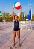 Het meisje leidt met de bal op om volleyball in de pool bij zon te spelen Royalty-vrije Stock Afbeelding