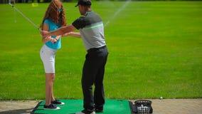 Het meisje leidt op om de bal in golf te raken stock footage