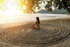 Het meisje leunt op het zandige strand in het centrum van een onvoorbereide cirkel achterover en mediteert stock foto