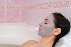 Het meisje ligt in de badkamers met een masker op haar gezicht Royalty-vrije Stock Afbeeldingen
