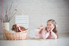 Het meisje ligt dichtbij een mand met konijn Stock Afbeelding