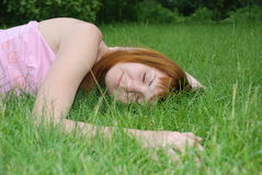 Het meisje ligt o het gras Royalty-vrije Stock Afbeeldingen