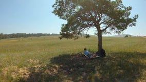 Het meisje ligt onder een boom en trekt een landschap op het gebied stock videobeelden