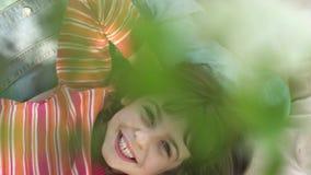 Het meisje ligt onder een tot bloei komende Apple-boom en glimlacht stock videobeelden